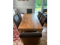 Oak furniture land solid mango wood dining table and six leather chairs.