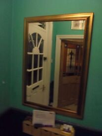A Large Gold Framed Beveled Mirror.