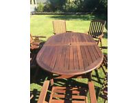 HARDWOOD EXTENDABLE GARDEN TABLE AND 8 RECLINING CARVER CHAIRS IN EXCELLENT HARDLY USED CONDITION