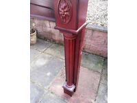 Fireplace surround. Solid piece of decorative furniture. Made from wood with a red/brown finish.