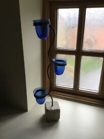 Blue glass candle holder on metal stand with concrete base.