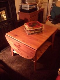 Large, dropleaf, solid wood, coffee table with shelf below. Square to oval shape.