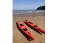 Two Pyranha Orca sea kayaks with paddles and neoprene cockpit travel covers