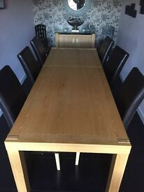 Extendable oak dining table with 6 dark brown leather chairs.