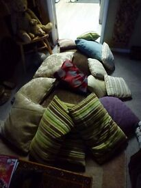 An assortment of feather cushions with covers, various sizes from large to small