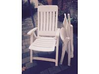 Two White Plastic Folding Chairs