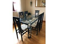 Glass table with 6 chairs and sideboard