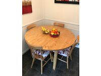 Circular pine dining table with 4 pine chairs. Will seat 6