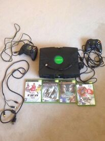 xbox with wires, controllers, and games