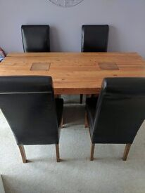 Solid oak dining table with brown leather chairs
