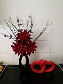 Red and black artificial dragon flowers in vase and decorative red hearts
