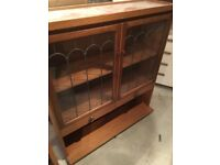 Wooden storage cabinet, glass paned doors.
