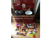 wooden toy kitchen with Melissa and Doug cookie set, wooden and felt toy foods, and tea set