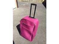Shocking pink large wheely suitcase £4 - grab a bargain for your holiday