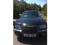 Black automatic Chrysler 300c estate with tinted windows and alloy wheels