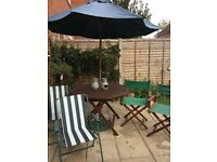 Buyer to collect . Wooden table 110cms diameter, parasol and cast iron stand, 4 chairs