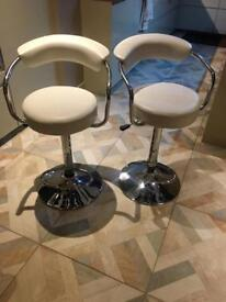 Two white bar stools with arms