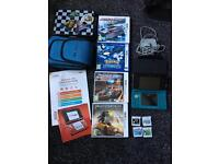 Nintendo 3ds in metallic aqua colour with games