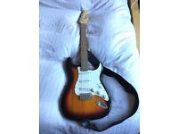 Squier Strat Electric Guitar plus Amplifier, electronic tuner and beginner music books.