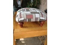 upholstered colourfulin grey white and tan footstool with wooden feet