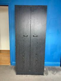 Dark brown/Black two door oak wardrobe.