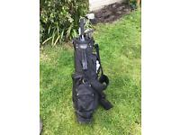 Golf clubs with bag, trolley and several balls
