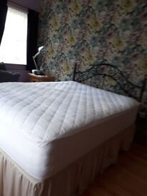Double bed with wrought iron headboard