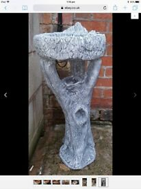 Large stone bird bath in shape of a tree trunk