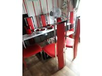 Black glass dining table and 6 chairs good condition.chairs are Red faux leather and chrome