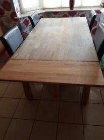 Extendable oak table and 4 brown faux leather chairs.