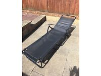 Two black reclining garden chairs, fold up for storage. In good condition.