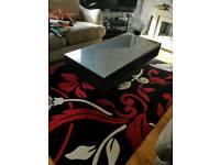 wooden dark grey coffee table with glass top and 2 storage shelfs