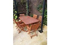 Garden table and six folding armchairs with cushions.