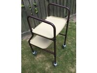 Brown/cream walking trolley with 2 shelves .