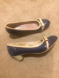 Women's size 5 navy pumps with brown details and small heel.