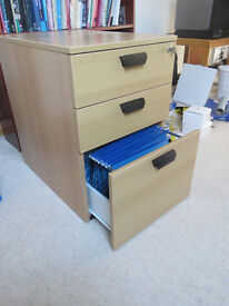 Small filing cabinet, fits under desk. 2 normal drawers, one with filing dividers. With key.