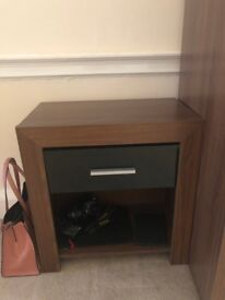 Dark wood bedside table with black glossy drawer