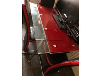 Red and clear glass dining room table with 4 red and black leather chairs