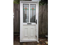 White UPVC door with twin leaded windows at the top
