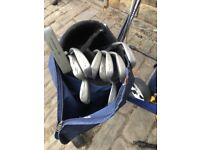 4 sets of golf clubs with bags and 3 trolleys