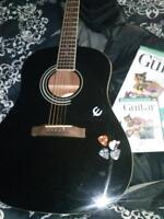 Black Epiphone acoustic guitar and accesories