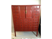 Deep red laquered wooden cabinet