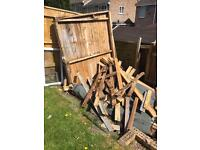 Pile of wood from dismantled shed and one side of shed