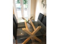 Glass dining table and four faux leather chairs