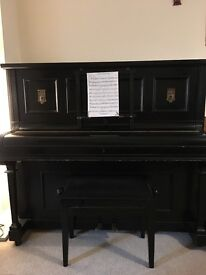 A black antique upright piano for sale