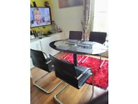 Glass Top Dining Table With Four Leather And Chrome Chairs Arm Rests