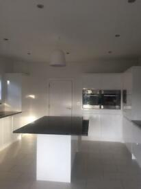 Complete white gloss kitchen appliances and black quartz worktops