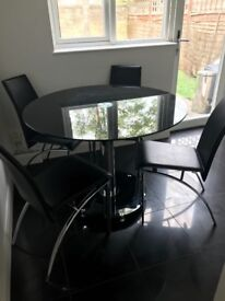 Round black glass and chrome table with four matching chairs