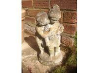 Boy girl kissing stone ornament
