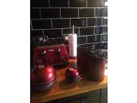 Red kitchen accessories including toaster, canisters, candle holders & kitchen roll holder